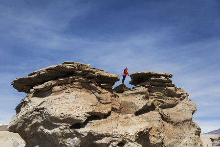 Young man at rock formations of Dali desert in Bolivia at Eduardo Avaroa Andean Fauna National Reserve in Bolivia