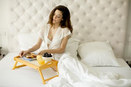 Bastante joven desayunando en la cama en el dormitorio