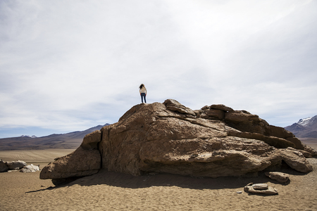 Young woman at ock formations of Dali desert in Bolivia at Eduardo Avaroa Andean Fauna National Reserve in Bolivia Stock Photo