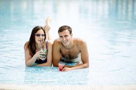 Young couple drinking cocktails in the swimming pool at summertime