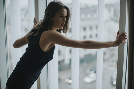 Pretty young woman in underwear standing by window in the room Stock Photo