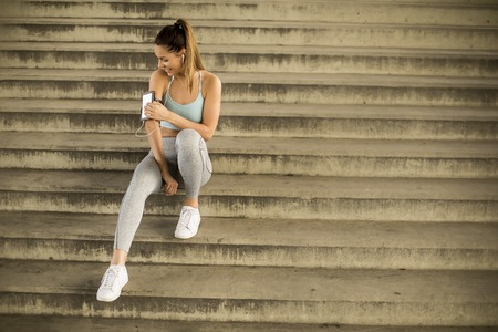 Portrait of pretty young female runner resting on stairs Stock Photo