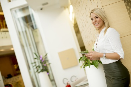 Young woman with mobile phone standing in the office Foto de archivo