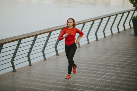 View at active young beautiful woman running in urban enviroment Stock Photo