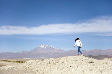 Young woman looking at Licancabur volcano in Reserva Nacional de Fauna Andina Eduardo Avaroa in Bolivia