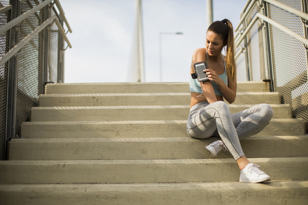 Portrait of pretty young female runner resting on the stairs