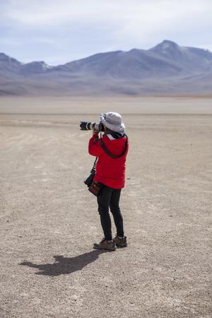 Young woman taking photo at Dali desert at Eduardo Avaroa Andean Fauna National Reserve in Bolivia Stock Photo