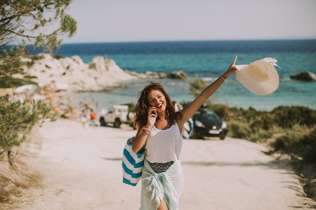 Pretty young woman with a bag using mobile phone on the beach at sunny summer day Reklamní fotografie