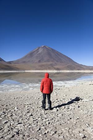 Young man looking at Laguna Verde lake and Licancabur volcano in Reserva Nacional de Fauna Andina Eduardo Avaroa in Bolivia
