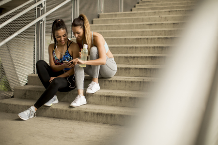 Portrait of pretty young females runner resting on stairs