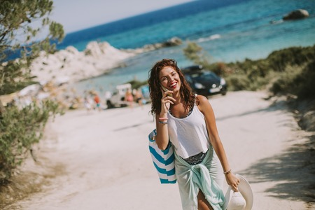 Pretty young woman with a bag using mobile phone on the beach at sunny summer day Archivio Fotografico