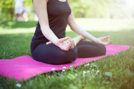 Woman in zen lotos yoga position on grass in park