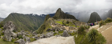 Unidentified people at remains of ancient Inca citadel in Machu Picchu, Peru.