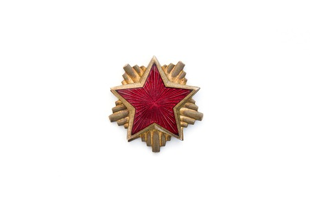 Old red star from communist military cap isolated on the white background