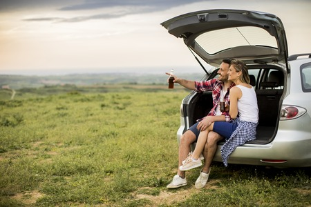Loving couple sitting in the car trank during trip in the nature Stock Photo