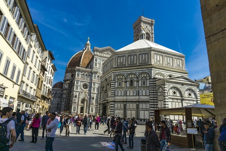 FLORENCE, ITALY - APRIL 6, 2018: Unidentified people by Santa Maria del Fiore cathedral in Florence, Italy. It is the main church of Florence and was opened at 1436.