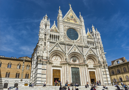 SIENA, ITALY - APRIL 8, 2018: Unidentified people in front of the Siena Cathedral, Italy. It is a medieval Roman Catholic Marian church now dedicated to the Assumption of Mary. Editorial