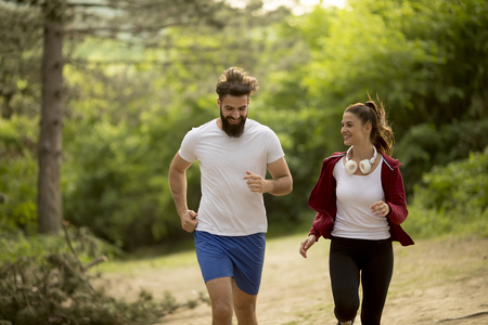 Young couple jogging outdoors in nature
