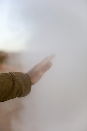 Hand of young man touching steam at Geysers Sol de Manana at Eduardo Avaroa Andean Fauna National Reserve in Bolivia