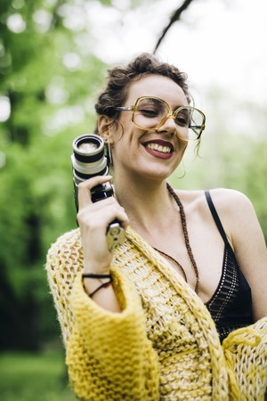 Portrait of young woman using an vintage cinema camera in a park