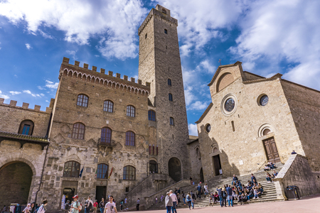 SAN GIMIGNANO, ITALY - APRIL 8, 2018: Unidentified people on Piazza del Duomo at San Gimignano, Italy. Historic Centre of San Gimignano