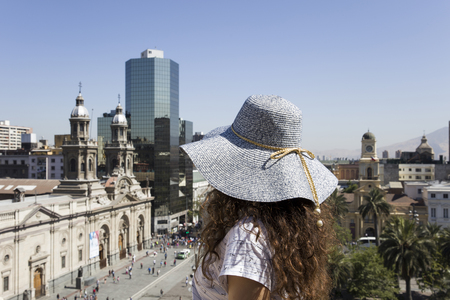 Young woman with hat looking at Santiago Chile on a sunny day
