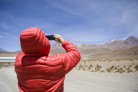 Young man taking photo at lagoon and mountains at Eduardo Avaroa Andean Fauna National Reserve in Bolivia Фото со стока