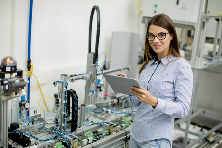 Pretty young woman with digital tablet in the electronics workshop
