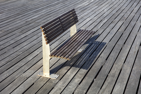 Perspective view at bench on the wooden boardwalk