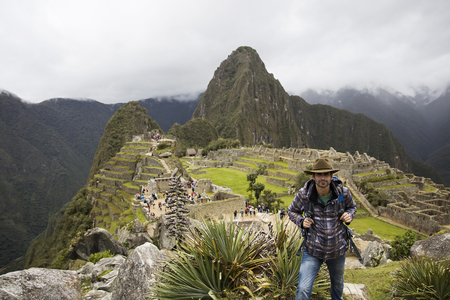View at young man at Machu Picchu Inca ruins in Peru