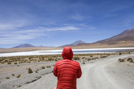 Young man lookinag at lagoon and mountains at Eduardo Avaroa Andean Fauna National Reserve in Bolivia Фото со стока