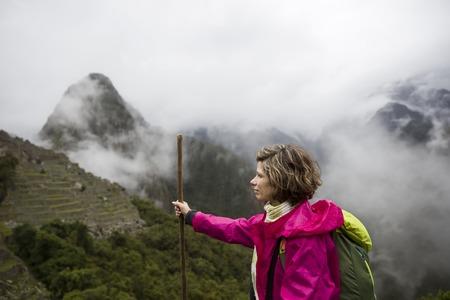 Young woman walking at Machu Picchu Inca ruins in Peru 写真素材