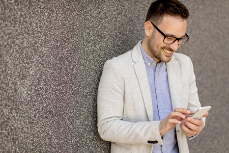 Young businessman in formal wear using mobile phone outdoor by wall