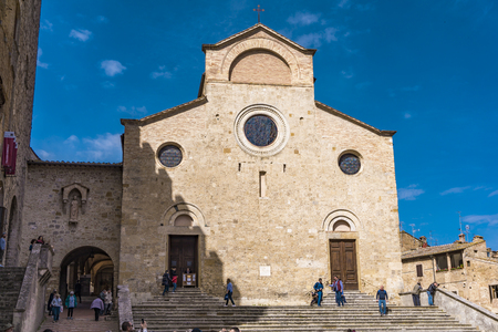 SAN GIMIGNANO, ITALY - APRIL 8, 2018: Unidentified people on Piazza del Duomo at San Gimignano, Italy. Historic Centre of San Gimignano is designated as UNESCO World Heritage Site since 1990.