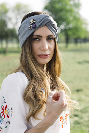 Portrait of young woman with turban on head and posing outdoor in the park