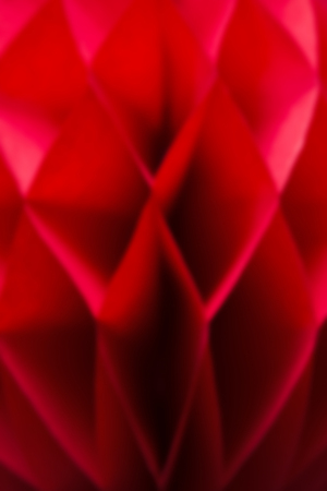Closeup detail of the blurred red honeycomb pom-pom paper ball decoration