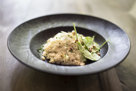 Close up view at risotto with gem fit and levisticum celery on a wood table composition