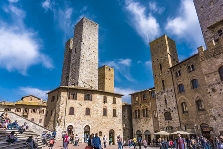 SAN GIMIGNANO, ITALY - APRIL 8, 2018: Unidentified people at Piazza del Duomo in San Gimignano, Italy. Historic Centre of San Gimignano is designated as    Site since 1990.