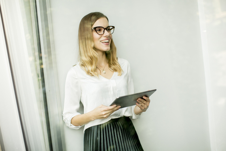Young attractive female manager working on digital tablet while standing in modern office