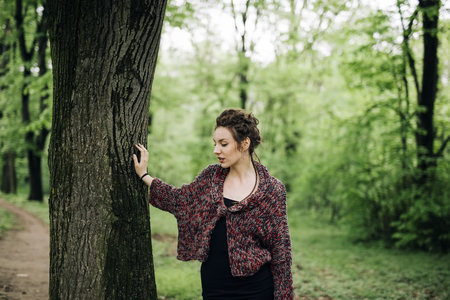 Portrait of young woman standing in the park by tree