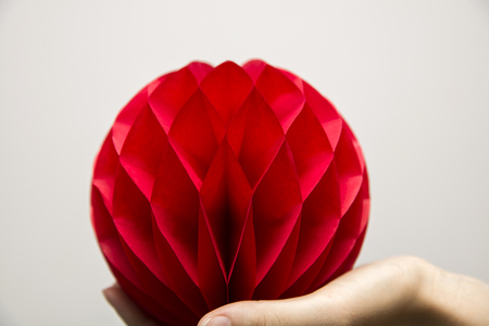 Red honeycomb pom-pom paper ball decoration on the human hand