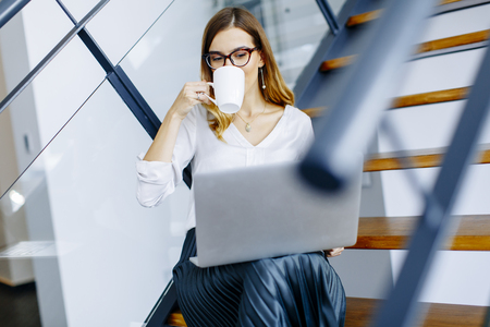 Young woman drinking coffe and working on laptop in the office