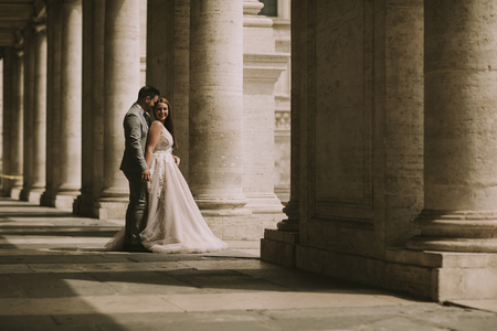 Young attractive newly married couple walking and posing in Rome with beautiful and ancient architecture on the background on their wedding day