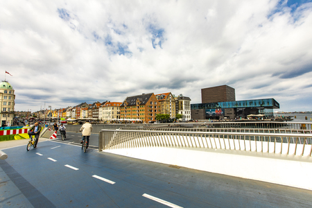 COPENHAGEN, DENMARK - JUNE 14, 2018: Unidentified people on Inderhavnsbroen bridge in Copenhagen, Denmark. It is combined pedestrian and bicyclist bridge opened at 2016. Imagens