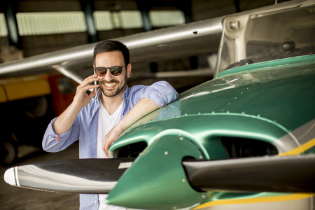 Handsome young pilot checking airplane  in the hangar