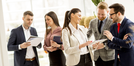 Meeting of group of businesspeople in the office standing in front of  large window in modern office