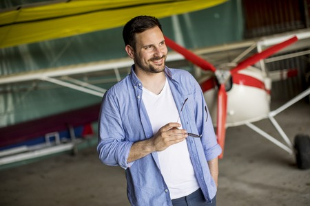 Handsome young man in the airplane hangar 版權商用圖片