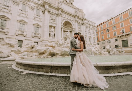 Just married bride and groom posing in front of Trevi Fountain (Fontana di Trevi), Rome, Italy 版權商用圖片