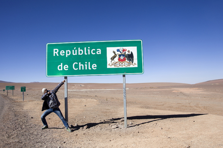 Young man pointing on the sign on Bolivia-Chile border Stock Photo