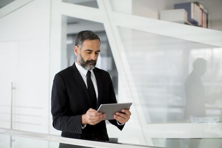Handsome middle age businessman with digital tablet in the modren office Foto de archivo